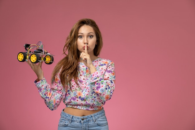 Front view young beautiful female in flower designed shirt and blue jeans holding toy car showing silence sign on pink background