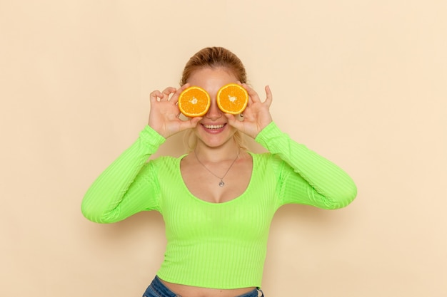 Front view young beautiful female in green shirt covering her eyes with oranges on the cream wall fruit model woman mellow
