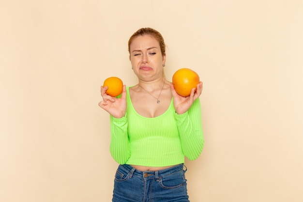 Front view young beautiful female in green shirt holding different sized fresh mellow oranges on cream wall fruit model woman mellow