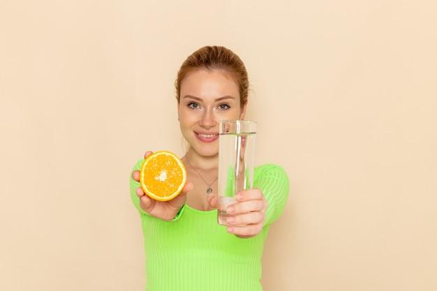 Vista frontale giovane bella femmina in camicia verde che tiene fetta d'arancia e bicchiere d'acqua sulla parete crema modello di frutta donna pastosa