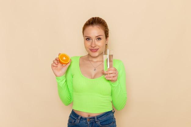 Vista frontale giovane bella femmina in camicia verde che tiene fetta d'arancia e bicchiere d'acqua sulla parete crema frutta modello donna mellow