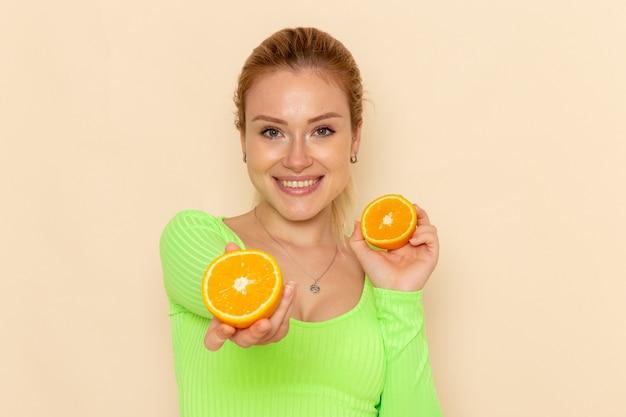 Giovane bella femmina di vista frontale in camicia verde che tiene le fette dell'arancia che sorride sulla donna di modello della frutta della parete crema pastosa