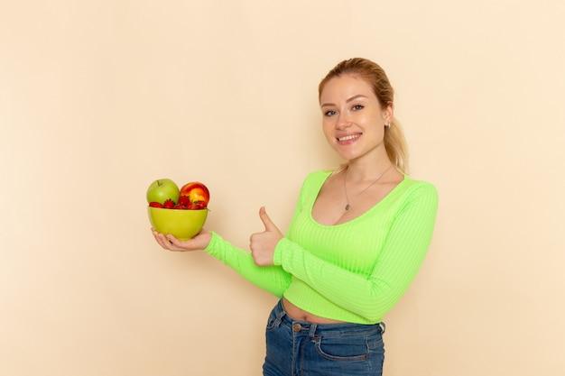 Giovane bella femmina di vista frontale in camicia verde che tiene piatto pieno di frutti sulla posa della donna del modello della frutta della parete crema chiara