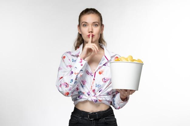 Вид спереди молодая красивая женщина, держащая корзину с картофельными чипсами на белой поверхности