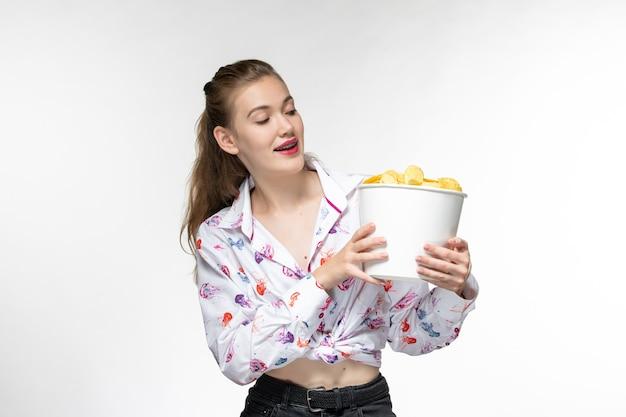 Vista frontale giovane bella femmina che tiene patatine fritte guardando film su superficie bianca leggera