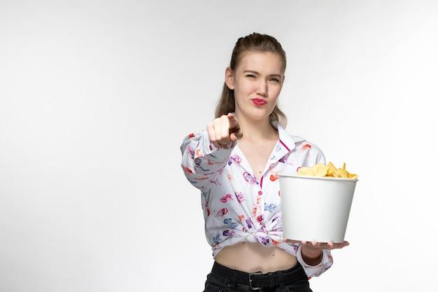 Вид спереди молодая красивая женщина, держащая картофельные чипсы, смотрит фильм на белой поверхности