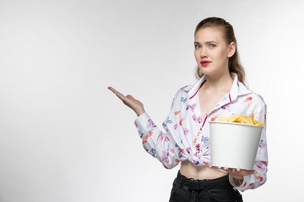 正面図明るい白い表面で映画を見ているジャガイモのcipsを保持している若い美しい女性
