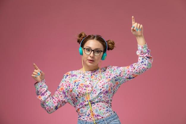 花の正面の若い美しい女性デザインのシャツとブルージーンズダンスとピンクの背景で音楽を聴く