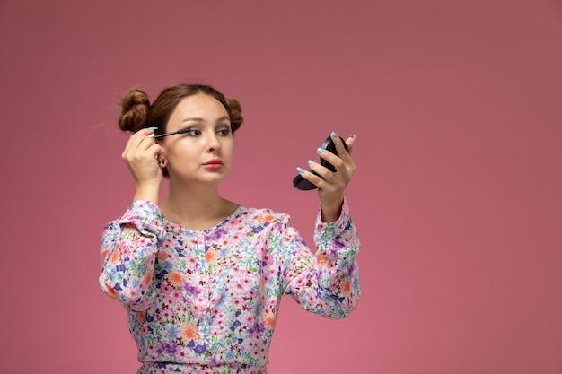 Вид спереди молодая красивая женщина в рубашке с цветочным дизайном и синих джинсах делает макияж на розовом фоне