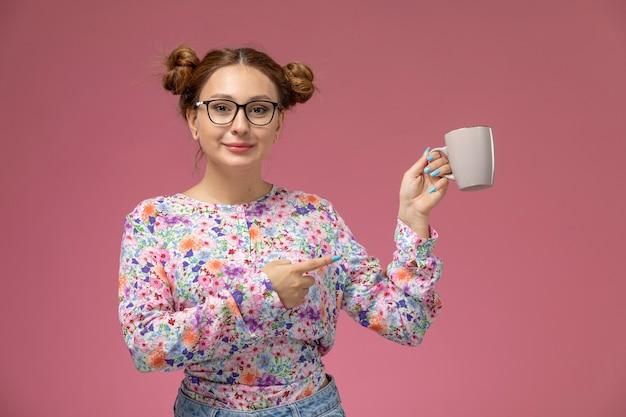Вид спереди молодая красивая женщина в рубашке с цветочным дизайном и синих джинсах, держащая чашку на розовом фоне