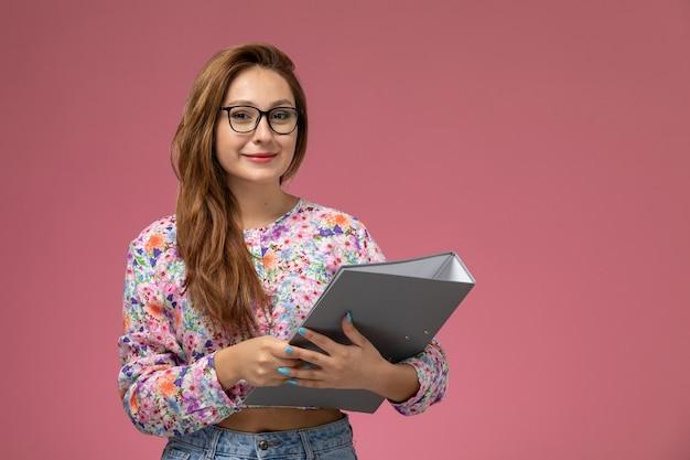 花の正面図の若い美しい女性デザインのシャツとピンクの背景に笑みを浮かべて灰色のドキュメントを保持しているブルージーンズ