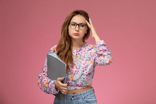 Вид спереди молодая красивая женщина в рубашке с цветочным дизайном и синих джинсах, держащая серый файл с подавленным выражением лица на розовом фоне