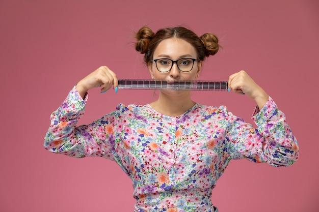 正面の若い美しい女性の花のデザインのシャツとピンクの背景に古い映画テープを保持しているブルージーンズ