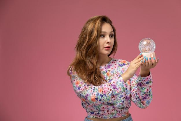Вид спереди молодая красивая женщина в цветочной рубашке и синих джинсах держит круглую стеклянную игрушку на розовом фоне