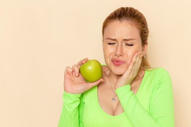 녹색 사과를 들고 크림 벽 과일 모델 여자에 치통을 갖는 녹색 셔츠에 전면보기 젊은 아름 다운 여성 부드러운