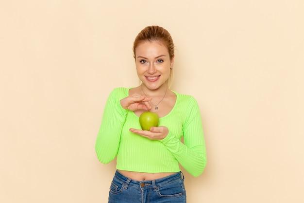Вид спереди молодая красивая женщина в зеленой рубашке держит зеленое свежее яблоко на кремовой стене фруктовая модель женщина