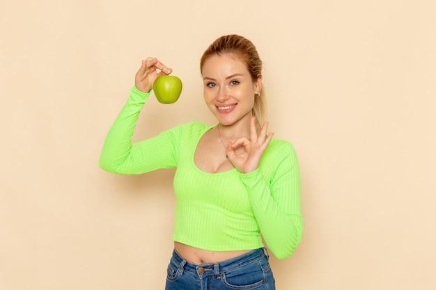 Вид спереди молодая красивая женщина в зеленой рубашке, держащая зеленое свежее яблоко, улыбаясь на сливочном столе, фрукты, модель, женщина, спелая