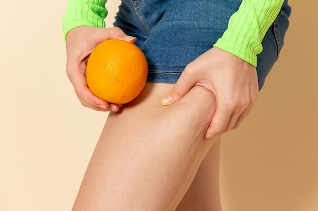 Вид спереди молодая красивая женщина в зеленой рубашке держит апельсин на кремовой стене фруктовая модель женщина спелая