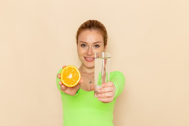 Вид спереди молодая красивая женщина в зеленой рубашке держит дольку апельсина и стакан воды на кремовой стене фруктовая модель женщина спелая