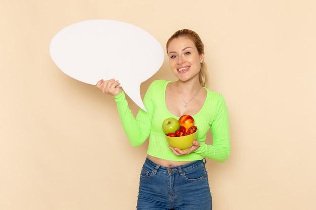 Вид спереди молодая красивая женщина в зеленой рубашке, держащая тарелку, полную фруктов и белый знак на кремовой стене, модель фруктов, женщина, еда, витаминный цвет