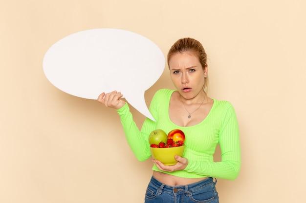 正面図緑のシャツの若い美しい女性は、クリーム色の壁に果物と白い看板がいっぱいのプレートを保持しています果物モデル女性食品ビタミン色