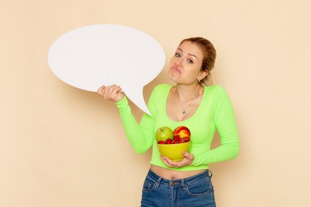 正面図果物とクリーム色の壁に白い看板がいっぱいの緑のシャツ保持プレートの若い美しい女性フルーツモデル女性食品ビタミン色