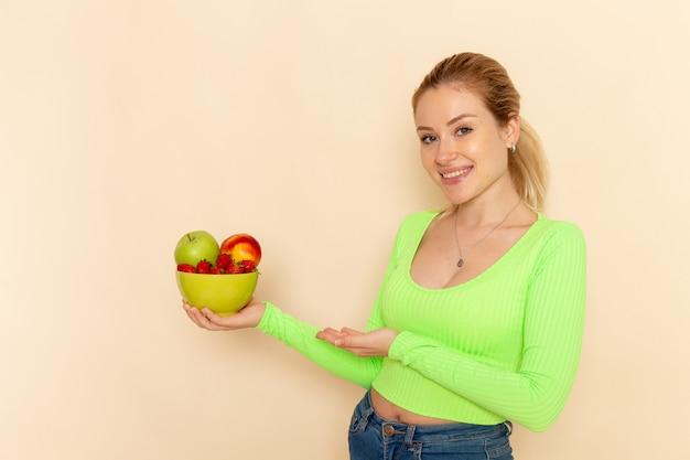 Вид спереди молодая красивая женщина в зеленой рубашке, держащая тарелку, полную фруктов на светлой кремовой стене, модель фруктов позы женщины