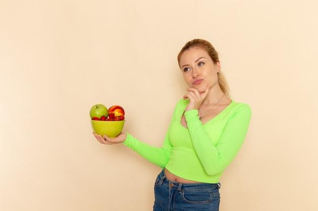Вид спереди молодая красивая женщина в зеленой рубашке, держащая тарелку, полную фруктов, думая о светлой кремовой стене, модель фруктов, поза женщины