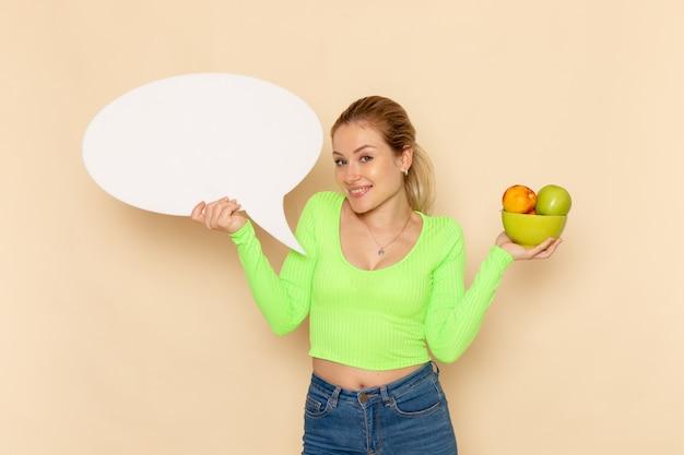 Вид спереди молодая красивая женщина в зеленой рубашке, держащая тарелку, полную фруктов с белым знаком на кремовой стене, модель фруктов, женщина, витамин