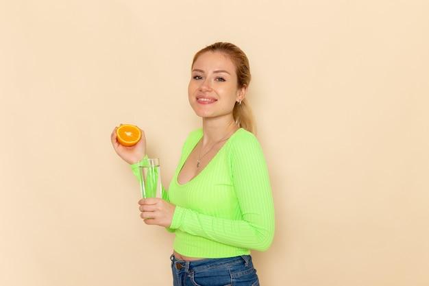 Вид спереди молодая красивая женщина в зеленой рубашке, выжимающая апельсиновый сок в стакан воды, улыбаясь на кремовой стене, модель фруктов, женщина, спелая