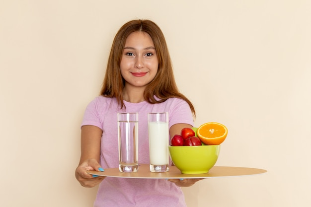 正面にピンクのtシャツとグレーのトレイフルーツミルクと水を保持しているブルージーンズの若い美しい女性