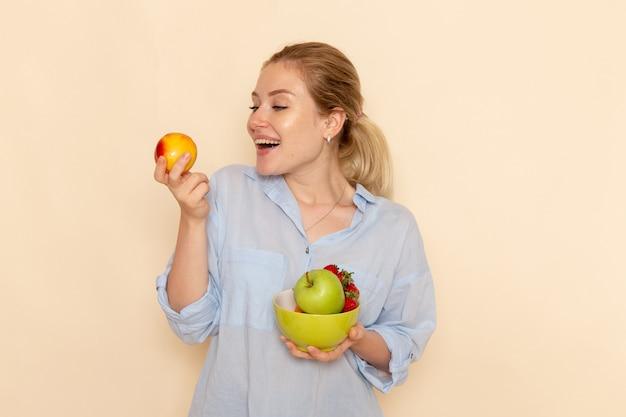 正面図クリーム色の壁に果物とリンゴとプレートを保持しているシャツの若い美しい女性フルーツモデルの女性のポーズ