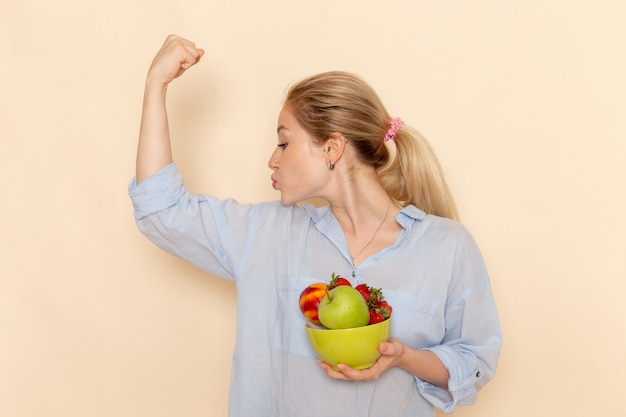 果物とプレートを保持し、クリーム色の壁に屈曲するシャツの若い美しい女性の正面図果物熟したモデルの女性のポーズ