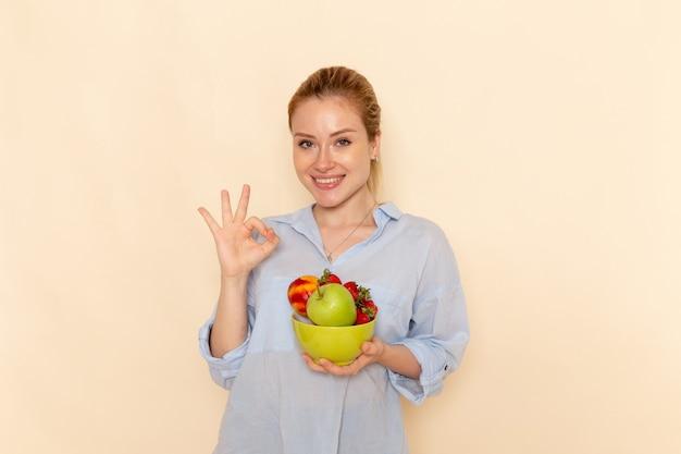 正面図クリーム色の壁に大丈夫な兆候を示す果物とシャツの保持プレートの若い美しい女性果物熟したモデルの女性のポーズ