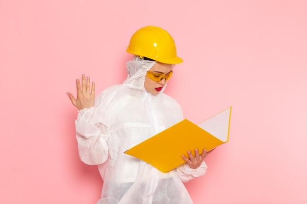 Вид спереди молодая красивая женщина в специальном белом костюме в защитном шлеме, держащая файл yellwo на розовом космическом специальном костюме