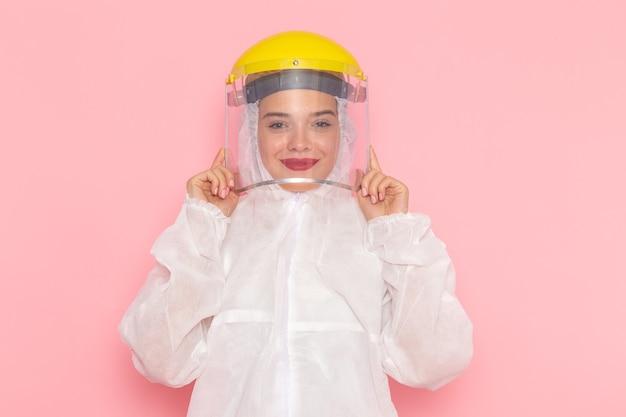 特別な黄色いヘルメットを着用し、ピンクのスペースに笑みを浮かべて特別な白いスーツの正面の若い美しい女性特別なスーツの女の子の女性