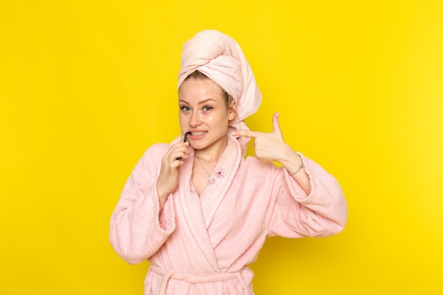 A front view young beautiful female in pink bathrobe cleaning her teeth