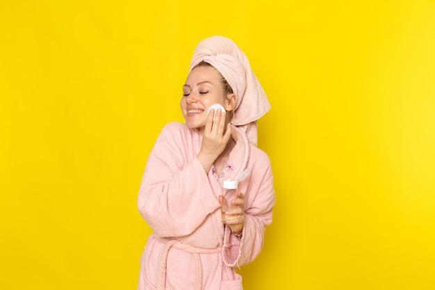 Una giovane bella femmina di vista frontale in accappatoio rosa che pulisce tutto il trucco con il sorriso