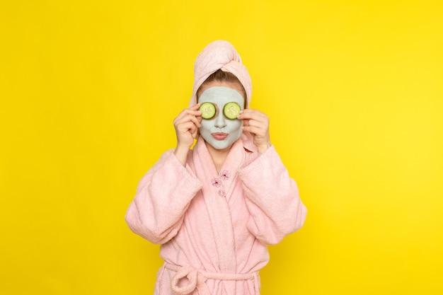 Una giovane bella femmina di vista frontale in accappatoio rosa che tiene le fette di cetriolo