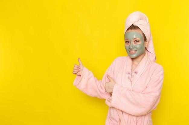 Una giovane bella femmina di vista frontale in accappatoio rosa che sorride e che posa