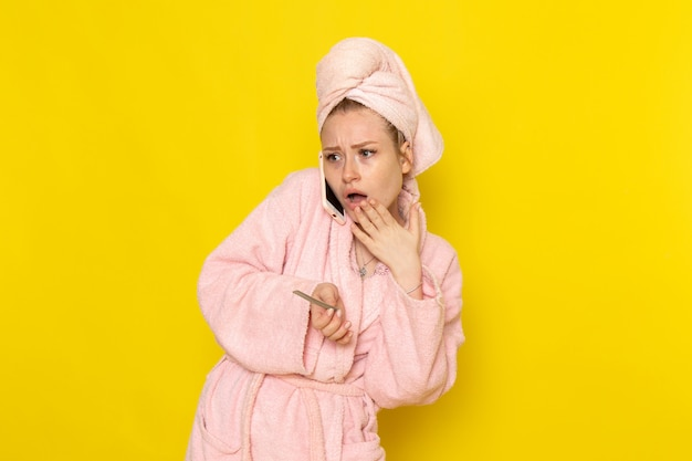 A front view young beautiful female in pink bathrobe talking on the phone