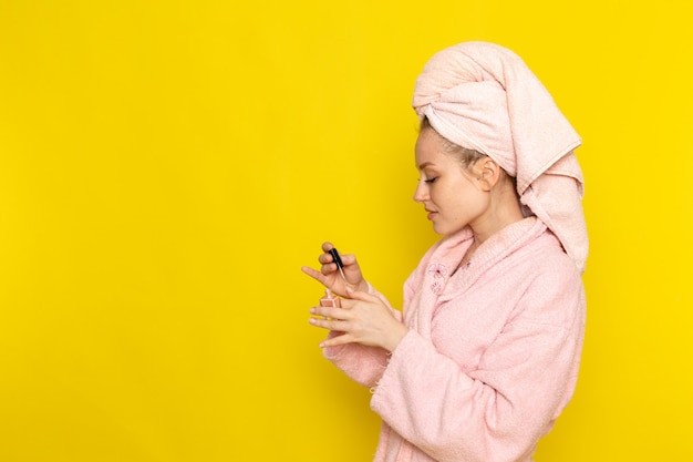 A front view young beautiful female in pink bathrobe using nail polish
