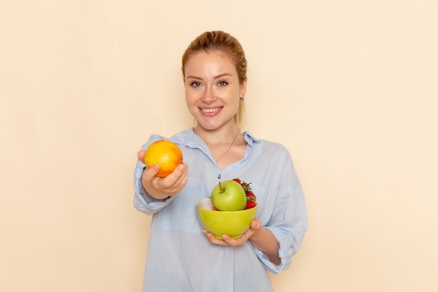 Front view young beautiful female in shirt holding plate with fruits on cream wall fruit model woman pose