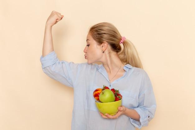 Giovane bella femmina di vista frontale in camicia che tiene il piatto con la frutta e che flette sulla posa della donna di modello maturo della frutta della parete crema