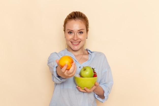 Vista frontale giovane bella femmina in camicia tenendo il piatto con la frutta con un leggero sorriso sulla parete crema frutta modello maturo donna posa
