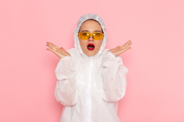 Front view young beautiful female in special white suit wearing special sunglasses with surprised expression on the pink space special suit  girl woman