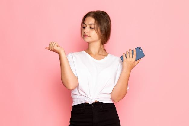 Una giovane bella femmina di vista frontale in camicia bianca che tiene un telefono