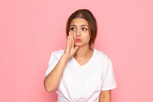 Una giovane bella femmina di vista frontale in camicia bianca che posa e che bisbiglia