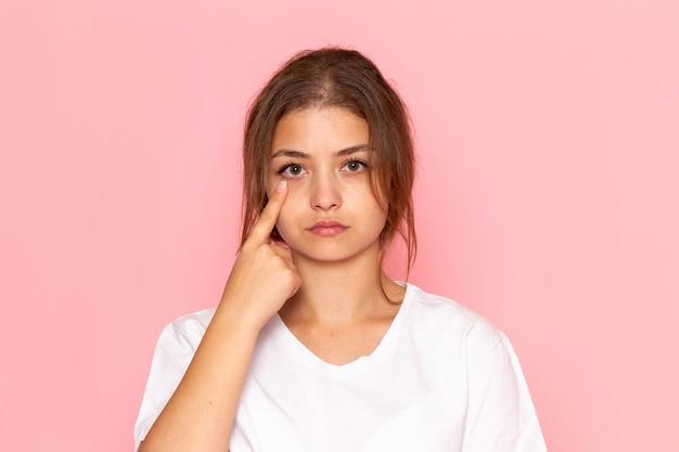 Una giovane donna bella vista frontale in camicia bianca che mostra il suo occhio