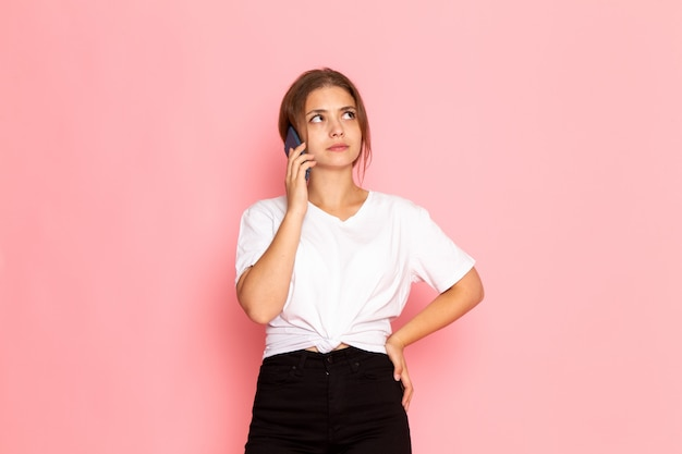 Una giovane bella femmina di vista frontale in camicia bianca che parla sul telefono